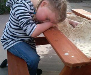 child asleep in the sandpit showing disturbed sleep pattern with SMS