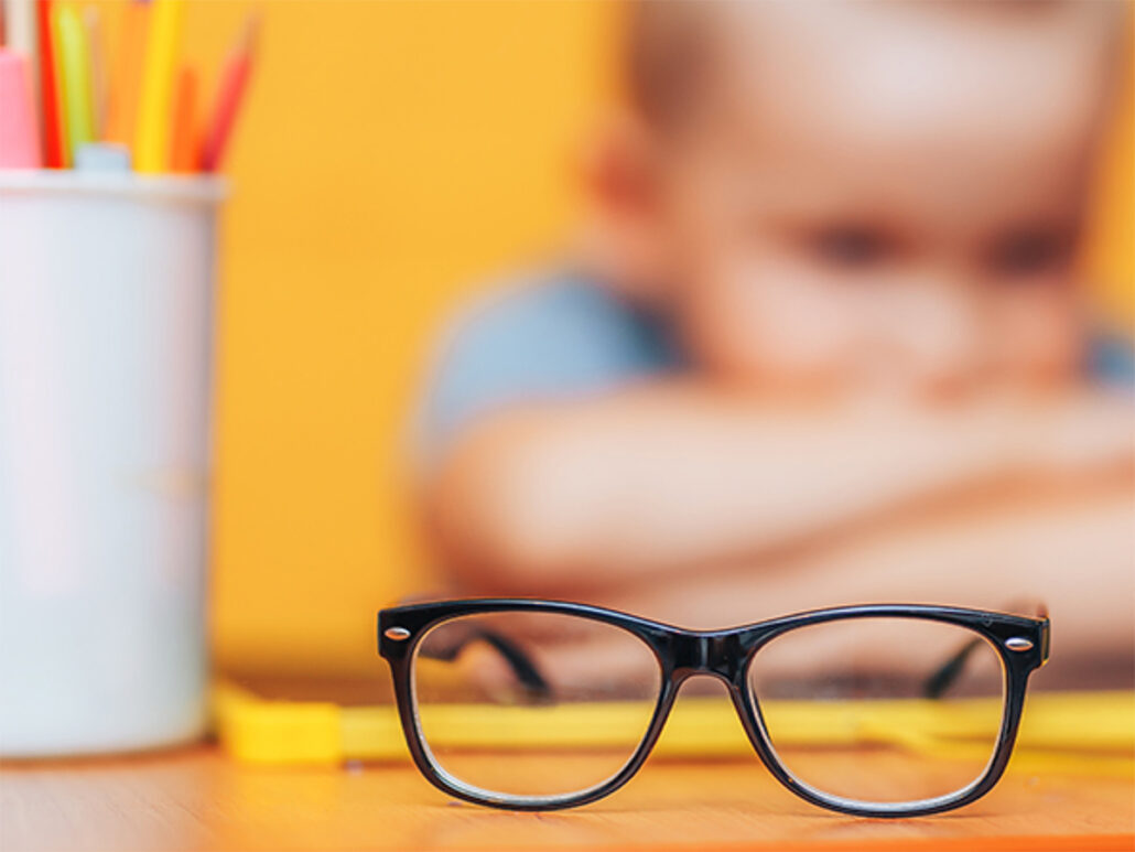 concept image of myopia with a boy furthest from the viewer unfocussed, and glasses closest to the view in focus
