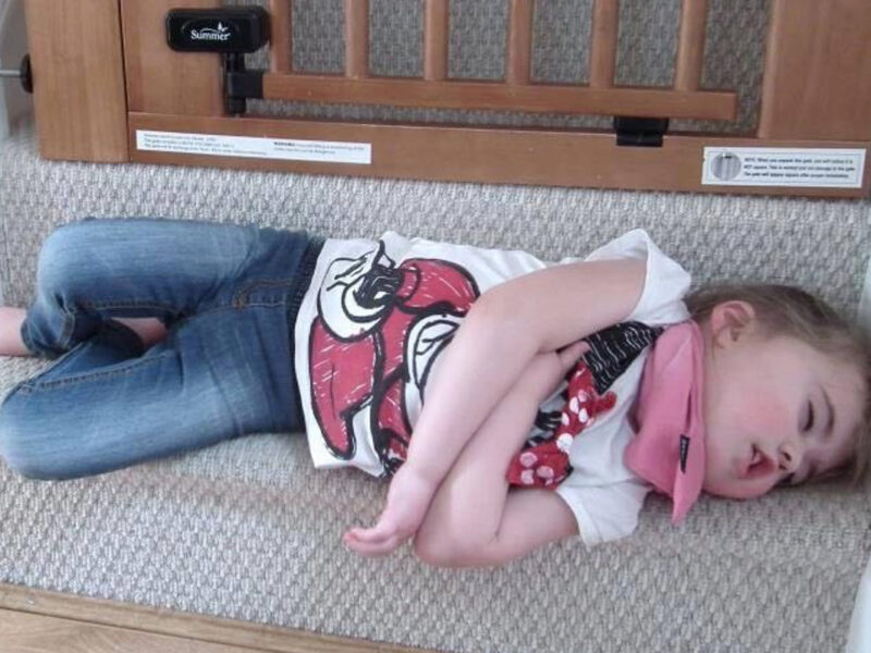 child asleep at bottom of stairs